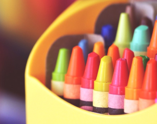 Bright yellow packet of different coloured crayons with decorative origami overlaid in the corners